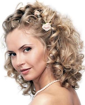 Peinado de novia semirrecogido con pelo rizado adornado con flores